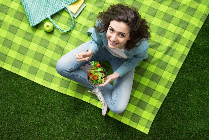 woman sitting cross-legged smiling eating salad